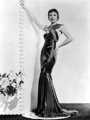 1934: Claudette Colbert (1903 - 1996), originally Claudette Lily Chauchoin, poses in a shimmering gown, designed by Travis Banton for the film 'Cleopatra' directed by Cecil B deMille.